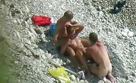 Horny girl plays with two dudes on the beach